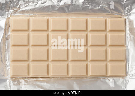 Whole bar of white milky chocolate in an open metalic foil packaging - Stock Image