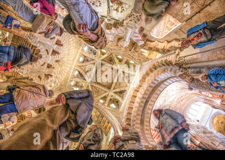 Low angle view of visitors below the dome of the Chapel of Villaviciosa, a 15th century Christian work inside the moorish Mosque of Cordoba, Spain. - Stock Image