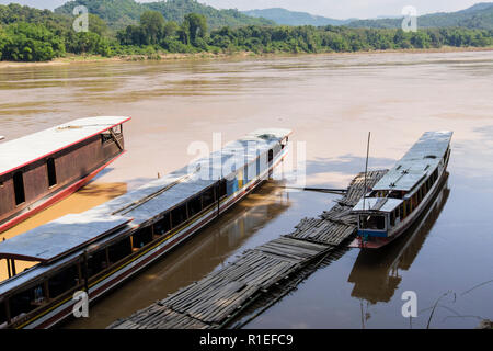 High view of tourists boats moored by wooden jetty at Pak Ou or Tham Ting Caves on Mekong River. Pak Ou, Luang Prabang province, Laos, southeast Asia - Stock Image