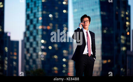 Businessman talking on cellphone in city at night - Stock Image