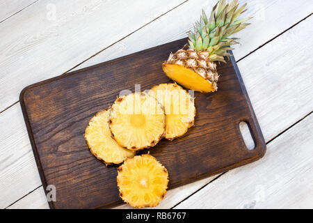 Sliced pineapple on brown and white wooden table. Center - Stock Image