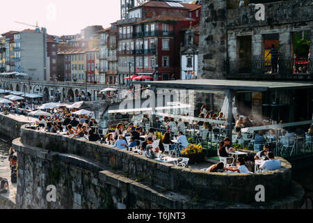 Porto, Portugal. April 29, 2019. Historic Porto bars and restaurants in famous Ribeira neighborhood attract tourists from all over the world - Stock Image