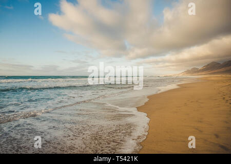 Lonely beach with beautiful mountain background  with cloudy sky - summer tropical vacation concept in free sandy scenic place with nobody there - Stock Image