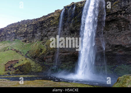 Iceland: Waterfall flowing down on moss rock - Stock Image