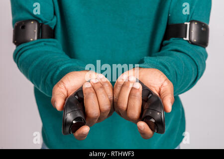 Hands of dark- skinned man holding gamepads from virtual reality headset. Grey background. VR technology gadget. - Stock Image