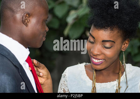 Smiling young woman arranges the tie of his friend whom he observes - Stock Image
