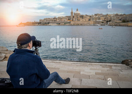 man taking landscape photos with a camera and a tripod, Valletta, Malta. - Stock Image