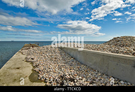 PORTGORDON MORAY SCOTLAND A JETTY IN THE HARBOUR COVERED WITH SHINGLE STONES DUE TO WAVE ACTION - Stock Image
