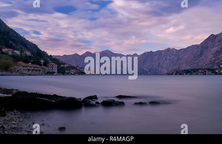 sunset in bay of Kotor Montenegro.   Water appears flat with rocks in anchor, and puffy clouds, in a bay surrounded by jagged glowing mountain - Stock Image