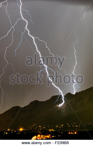 A huge lightning bolt strikes the side of the Santa Catalina Mountains near Pusch Ridge at night a summer monsoon - Stock Image