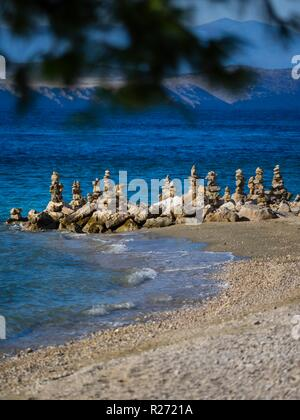 Stack of rocks on beach behind pine trees forest branches trees - Stock Image
