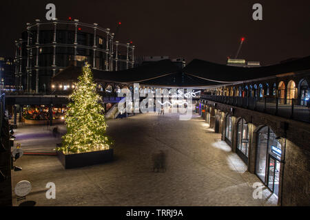 London, England, UK - December 14, 2018: People walk past Christmas decorations at the Coal Drops shopping centre in London's King's Cross regeneratio - Stock Image