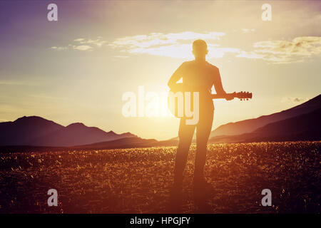 Man stands with guitar at sunset and mountains bacgdrop. Travel music concept - Stock Image