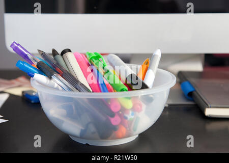 Pens, highlighters, and markers in front of a computer and journal at work or home - Stock Image