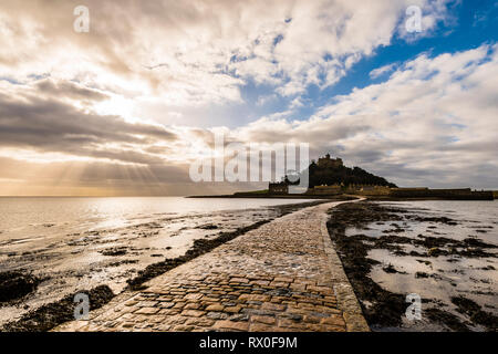 Sunburst over causeway at St Michael's Mount, Cornwall, UK - Stock Image