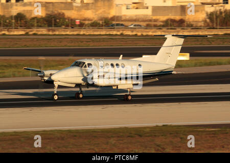 Beechcraft Super King Air 300 small private twin-engine turboprop commuter plane on the runway after landing in Malta at sunset - Stock Image