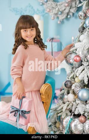 A child in the studio for the New Year. Girl in a Christmas photo session. Festive mood. Waiting for a miracle in the Birth. - Stock Image