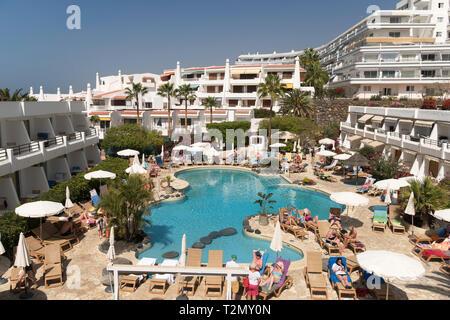 People sunbathing around the swimming pool of the Hovima Panorama Hotel in Costa Adeje, Santa Cruz de Tenerife, Spain - Stock Image