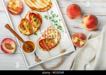 Bread toast with grilled peaches, ricotta or mascarpone cheese, honey and thyme. Delicious fruit Breakfast for gourmets. Selective focus - Stock Image