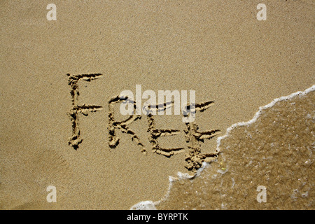 'Free' written out in wet sand. Please see my collection for more similar photos. - Stock Image