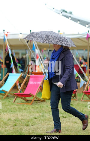 Hay Festival, Hay on Wye, Powys, Wales, UK - Wednesday 29th May 2019 - A visitor shelters under her umbrella on a very cold and wet day at the Hay Festival with temperatures of only about 11c - Credit: Steven May/Alamy Live News - Stock Image