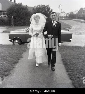 1960s, historical, father walking with bride, having recently arrived in  the bridal car, a small vauxhall, England, UK. - Stock Image
