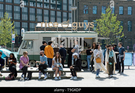Rice Guys Stall with young, cool and trendy people queuing and sitting on bench in front, Granary Square Kings Cross London Borough of Camden, England - Stock Image