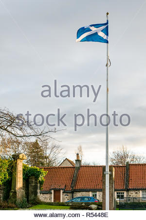 Athelstaneford, East Lothian, Scotland, United Kingdom. 29th Nov, 2018. UK Weather:Birthplace of St Andrew's Cross, the saltire flag. On the eve of St Andrew's Day the sun shines briefly to light up Athelstaneford Church and the historic doocot of the National Flag Heritage Centre. Legend says that on the eve of a battle between Picts and Angles from Northumbria in 832AD Saint Andrew had a vision of victory and when the Picts saw a white cross formed by clouds in a blue sky they attributed their victory to his blessing, adopting the cross as a flag - Stock Image