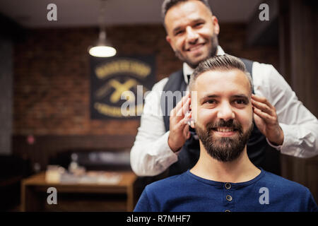 Handsome hipster man client visiting haidresser and hairstylist in barber shop. Copy space. - Stock Image