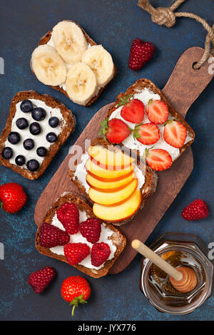 Diet breakfast. Toasts with cream cheese and fresh berries and fruits: banana, raspberry, blueberry, strawberry, peach. Top view - Stock Image