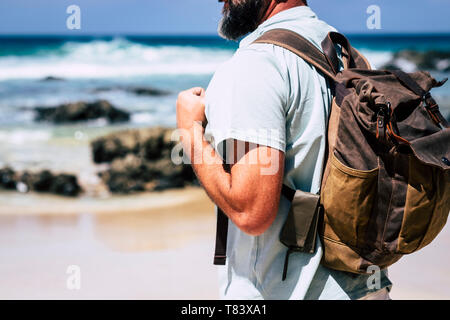 Close up of adult people caucasian man travel with leather style backpack - alternative traveler vacation outdoor concept and beach sea in background  - Stock Image