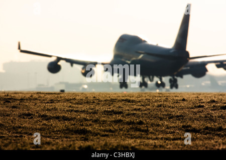 Commercial airliner landing at London Heathrow with condensation trails forming over the wings. - Stock Image