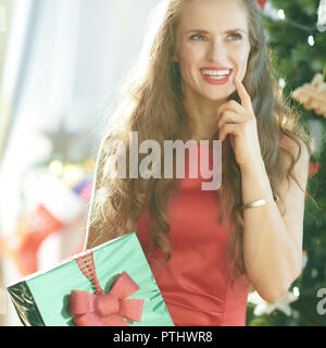 pensive stylish woman in red dress with green Christmas present box near Christmas tree - Stock Image