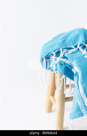 Blue and white striped cotton beach blanket with fringe folded on wooden stool on white wall background. Summer seaside vacation relaxation accessorie - Stock Image