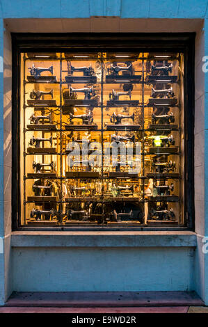 Antique sewing machine display in a Lincoln Road Mall retail shop window in Miami Beach, Florida, USA. - Stock Image