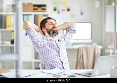 Happy relaxed businessman sitting by workplace with his hands behind head while enjoying short break in the middle of working day - Stock Image