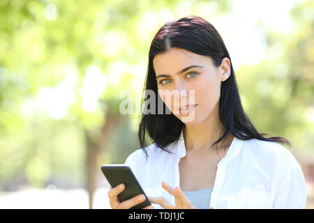 Serious adult woman holding smart phone looking at camera in a park with a green background - Stock Image