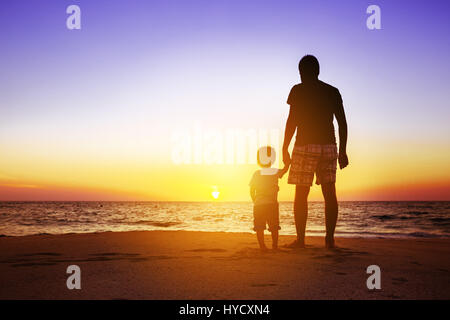 Father and son at sunset beach - Stock Image