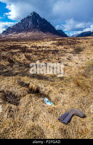 A wellington boot and plastic items dumped in an area of world class natural beauty on the boundary between Glen Coe and Glen Etive in Scotland - Stock Image
