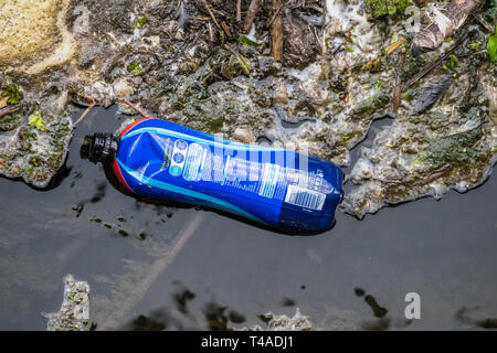 Plastic bottle waste polluting a waterway. - Stock Image