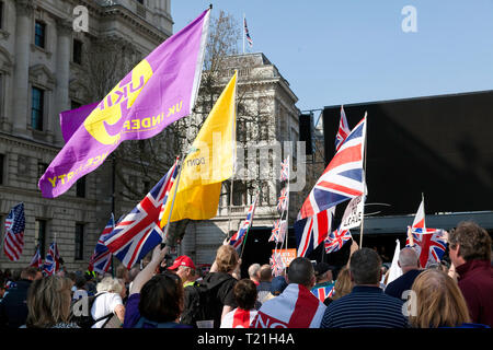 Protestors  with flags and banners, gather outside Parliament to demonstrate against the delay to Brexit  on the day the UK was due to  leave  the EU - Stock Image