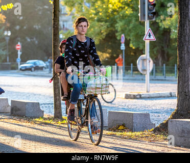Strasbourg, Alsace, France, woman with her son in child seat biking on pavement, - Stock Image