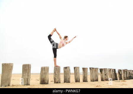 Young woman on the beach. Stretching - Stock Image