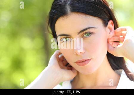 Portrait of a beauty woman with green eyes looking at you in a park - Stock Image