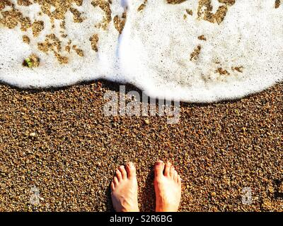 Looking down from above onto a pair of bare feet and toes standing on a pebble beach with surf and waves flowing and copy space - Stock Image