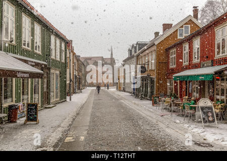 A small street full of cafes and bars in the town of Trondheim in Norway, during a snow storm. - Stock Image