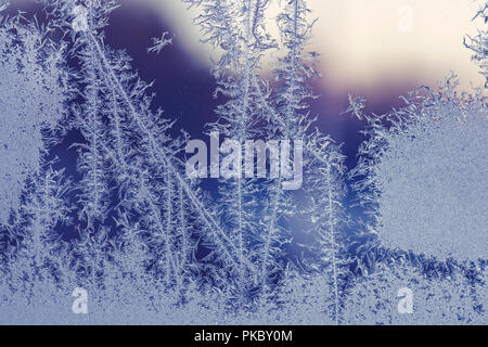 Hoarfrost on a window in the winter in beautiful snowflake patterns - Stock Image