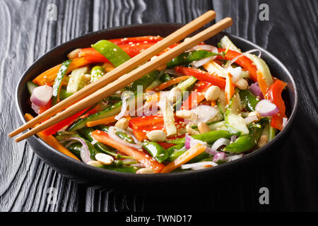Healthy vegetable salad with sesame and peanuts close-up on a plate on the table. Asian style. horizontal - Stock Image