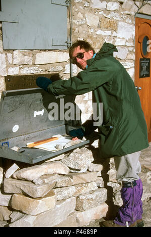 A hiker signs the summit book on the summit of Mount Whitney in the Sierra Nevada in California - Stock Image