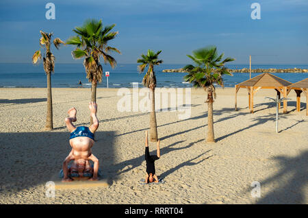 Young woman doing a headstand next to the Ben Gurion statue on the beach in Tel Aviv, Israel - Stock Image